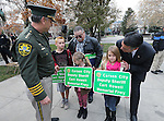 Sheriff Ken Furlong, left, and Gov. Brian Sandoval, right, give commemorative signs to the children of Carson City Sheriff's Dep. Carl Howell during a ceremony at the Nevada Law Enforcement Officers Memorial in Carson City, Nev., on Tuesday, Dec. 8, 2015. Officials unveiled a freeway sign dedicating I-580 in honor of Howell, who was killed in the line of duty Aug. 15, 2015. Howell's father Kevin is at rear. <br /> Photo by Cathleen Allison