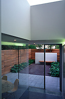 Looking from the interior out through sliding glass doors into the small urban garden