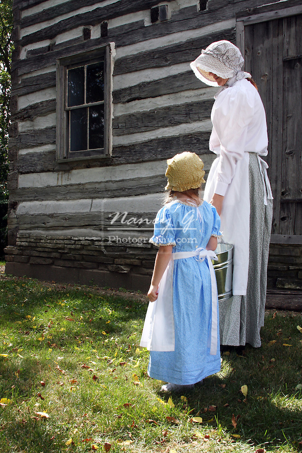 A mother and little girl walking with a milking pale by a log cabin