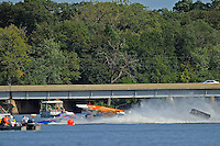 Frame 7: #37 Stacy Funk rolls over after contact with #31 Dan Schwartz (red and White boat with it's cowling in the air). Funk rolled completely over while it is speculated that Schwartz was knocked unconscious in the accident and accelerated across the river and crashed onto the golf course. In the later images of this series Schwartz can be seen emerging from behind Funk's boat. (SST-120 class)