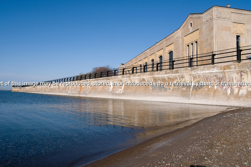 Sea Wall with railing on top and art deco building in background