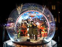 Kerstmarkt op het Damrak in Amsterdam. Mensen kunnen zich laten fotogreferen in een reuze snowball