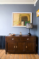 An abstract painting and black-and-white table lamp on a simple wooden cupboard in a corner of the living room