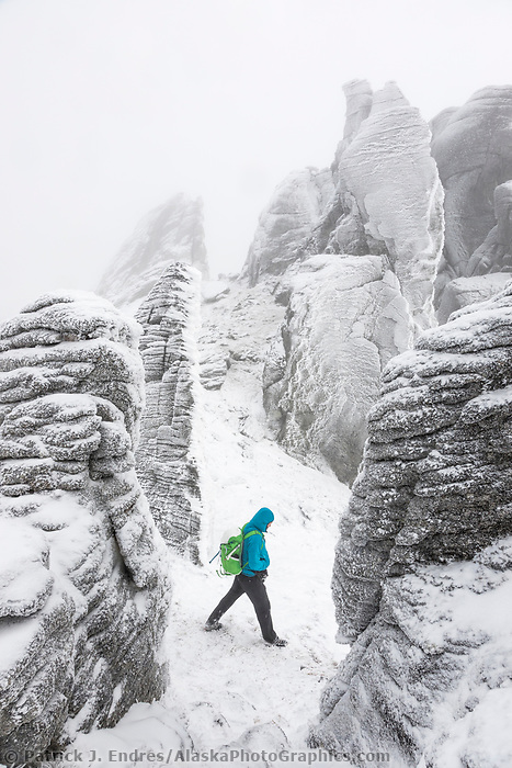 Hiker traverses around the hoar frost covered granite tors along the ridge to Mt. Prindle, Steese National Conservation Area, Interior, Alaska.