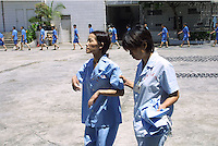 Ah Li, a 21 year-old female drug addict walks with another female drug addict in a drug rehabilitation centre in Bao'an, China. Ah Li moved to Shenzhen from northern China when just sixteen years old after the break-up of her family. She was tricked into prostitution and initially forced to take drugs until she became addicted and dependent on her gang bosses.