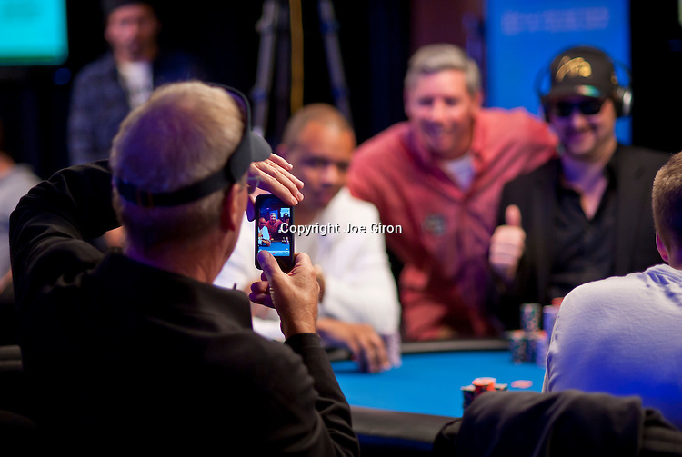 Bobby Baldwin takes a photo of Phil Ivey, Mike Sexton and Phil Hellmuth on his phone.