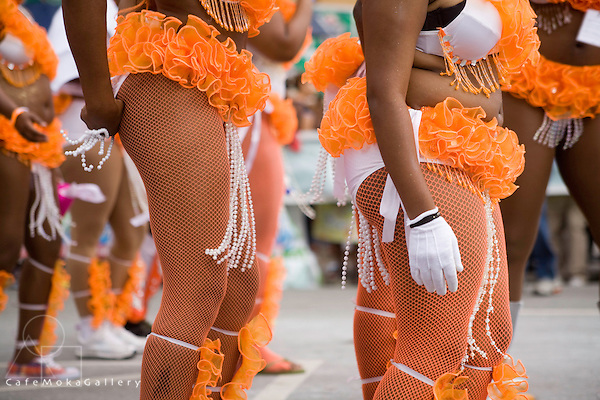 Trinidad Carnival, Detail of two masqueraders, women in orange fishnet tights, white gloves and beads