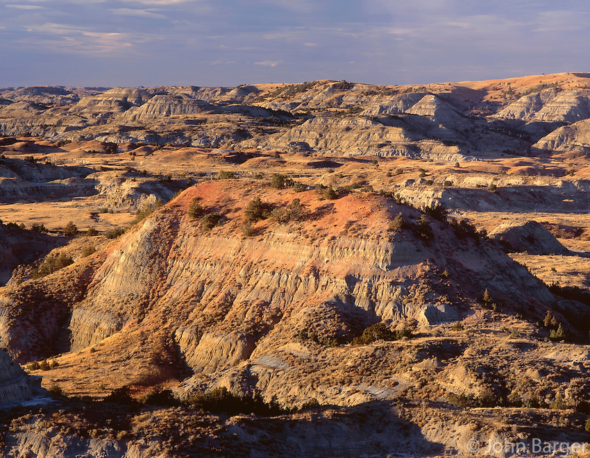 NDTR_122 - USA, North Dakota, Theodore Roosevelt National Park, Evening light defines eroded, sedimentary hills and grassy plains in autumn, Painted Canyon Overlook, South Unit.