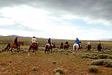 USA, Wyoming, Encampment, cowboys ride out on horseback to gather cattle for a branding, Big Creek Ranch