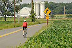 Cyclist on Creek Road with barn and farmland.