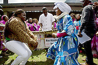 Switzerland. Canton Valais. St-Maurice. Africa Saints Pilgrimage (Pèlerinage aux Saints d'Afrique). Religious choirs coming from all over Switzerland sing, dance  and celebrate their faith and belief in Jesus  Christ. Two women dance on music payed by drums and balafon instruments. The balafon (bala, balaphone) is a resonated frame, wooden keyed percussion idiophone of West Africa. The balafon is part of the idiophone family of tuned percussion instruments. Sound is produced by striking the tuned keys with two padded sticks. The first part of the pilgrimage takes place in Véroliez which is a part of the the town of St-Maurice. 2.06.13 © 2013 Didier Ruef