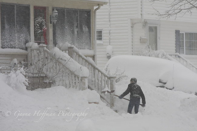 Teen shoveling front steps in snow storm.