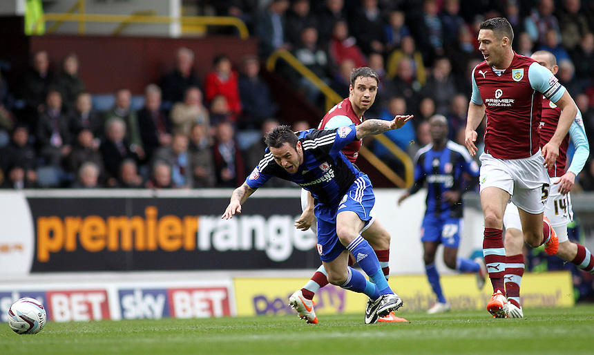 Middlesbrough&rsquo;s Lee Tomlin goes down under the challenge from Burnley's Michael Duff <br /> <br /> Photo by Rich Linley/CameraSport<br /> <br /> Football - The Football League Sky Bet Championship - Burnley v Middlesbrough - Saturday 12th April 2014 - Turf Moor - Burnley<br /> <br /> &copy; CameraSport - 43 Linden Ave. Countesthorpe. Leicester. England. LE8 5PG - Tel: +44 (0) 116 277 4147 - admin@camerasport.com - www.camerasport.com