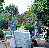 Dominic and Francesca Rowan and their sons at a table laid for lunch in the garden