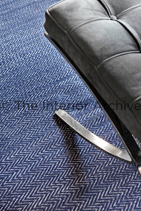 Detail of the blue and white herringbone pattern on the living room rug and a Mies van der Rohe chair