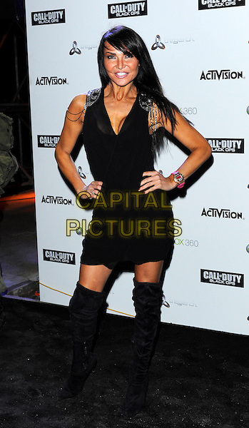 """LIZZIE CUNDY.Launch party for new video game """"Call Of Duty: Black Ops"""", Battersea Power Station, London, England, UK. .November 8th, 2010.full length black dress boots hands on hips.CAP/DH.©David Hitchens/Capital Pictures."""