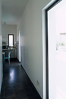This corridor has a polished slate floor and leads to the kitchen/dining area