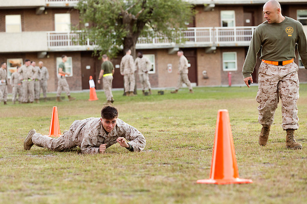 October 22, 2014. Camp LeJeune, North Carolina.<br />  SSgt. Jamil Alkattan, right, times a Marine in the Ground Combat Element Integrated Task Force as he participates in the belly crawl portion of the Combat Fitness Test (CFT). The CFT includes a half mile run, followed by a series of timed physical tests that simulate conditions they could encounter in combat situations.<br />  The Ground Combat Element Integrated Task Force is a battalion level unit created in an effort to assess Marines in a series of physical and medical tests to establish baseline standards as the Corps analyze the best way to possibly integrate female Marines into combat arms occupational specialities, such as infantry personnel, for which they were previously not eligible. The unit will be comprised of approx. 650 Marines in total, with about 400 of those being volunteers, both male and female. <br />  Jeremy M. Lange for the Wall Street Journal<br /> COED