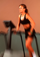 Attractive young woman exercising on a treadmill in a .