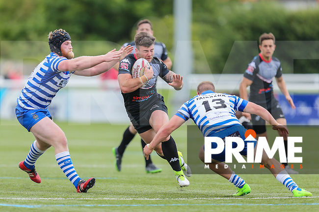 Andy Ackers of London Broncos (centre) looks to avoid the tackle from Murray of Halifax RLFC (left) and Jacob Fairbank of Halifax RLFC (right) during the Kingstone Press Championship match between London Broncos and Halifax RLFC at Castle Bar , West Ealing , England  on 4 June 2017. Photo by David Horn.