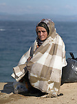 A Syrian refugee women waits for transportation after arriving on the beach near Molyvos, on the Greek island of Lesbos, on October 31, 2015. She and other refugees crossed the Aegean in small, overloaded boats, and local and international volunteers provided them with water, food, and dry clothing. The refugees will then proceed on their way toward western Europe. The boat to Greece was provided by Turkish traffickers to whom the refugees paid huge sums to arrive in Greece.