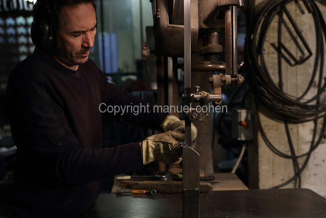 Nicolas Desbons, metalworker and artist, cutting sections of steel rod for use on a figurative sculpture, on a machine in his Soleil Rouge workshop, photographed in 2017, in Montreuil, a suburb of Paris, France. Desbons works mainly in steel but often in conjunction with other materials such as fibreglass, glass and clay, using both cold metal and forge techniques. He produces both figurative and abstract sculptures as well as furniture and lighting. Picture by Manuel Cohen