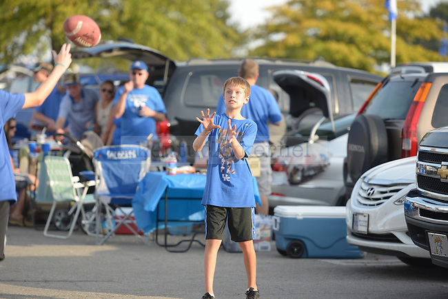 A young boy catches a ball outside of Commonwealth Stadium in Lexington, Ky., on Saturday, September 28, 2013. Photo by Eleanor Hasken | Staff