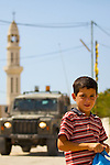 A palestinian boy walks past an Israel army jeep in the main square of the West Bank village of An Nabi Salih near Ramallah on 09/07/2010.