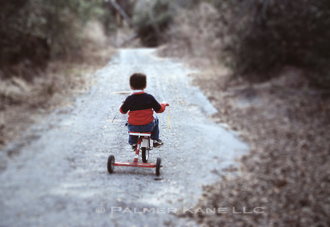 5 year old boy ventures down a deserted road on his trycycle