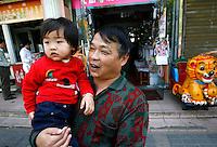 Li Fang (droite) porte sa petite-fille Li Siqi (gauche) lors d'une promenade dans leur quartier à Baoshan, près de Shanghai, le 7 mai 2008. A cette heure-là de la matinée, grands-parents et petits-enfants sont tous dans la rue. On voit des enfants réclamer une pièce à leurs aïeuls, qui mettent volontiers la main au porte-monnaie. Photo par Lucas Schifres/Pictobank
