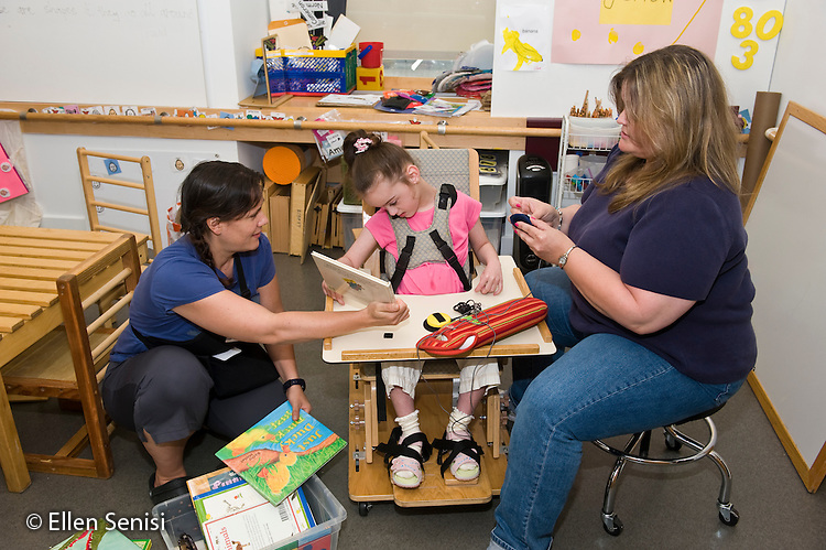 MR / New York, NY. Standing Tall: An educational program for students with neuromotor disablilities that uses the principals of conductive education, which combines a structured intensive program of daily physical training with traditional academic studies. ID: AI-gSst. Girl (6; Cerebral Palsy) in conductive education classroom chooses book she will have read to her. At left is her conductor (also a teacher and the school's director) and to her right is her speech language pathologist. On her tray is an augmentative and alternative communication device (AAC). MR: Dyc1, Sel4, Ski3. © Ellen B. Senisi
