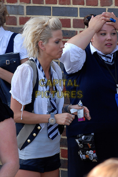 """SARAH HARDING.Filming on the set of """"St Trinian's: The Legend of Fritton's Gold"""", outside the Globe Theatre, London, England..August 10th, 2009.2 half length black grey gray top white shirt scarf striped stripes girls aloud profile watch funny face mini micro shorts food eating waistcoat beige film movie .CAP/IA.©Ian Allis/Capital Pictures."""
