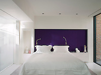 The purple bespoke, Stephanie Joy, unpholstered headboard brings a hint of warmth to the white interior