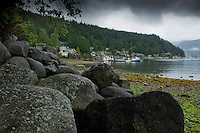 Sea weed covered beach and boulders against the background of clouds and trees in Deep Cove, Vancouver, British Columbia, Canada.