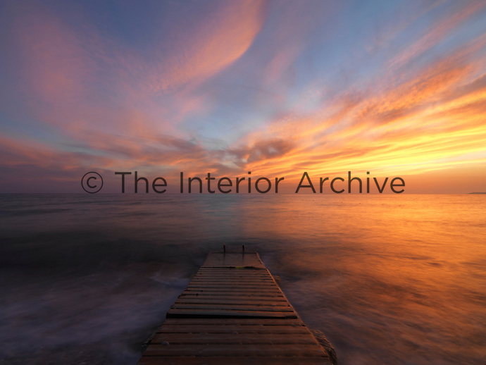 A dramatic Mediterranean sunset is photographed from an ancient jetty in Sicily