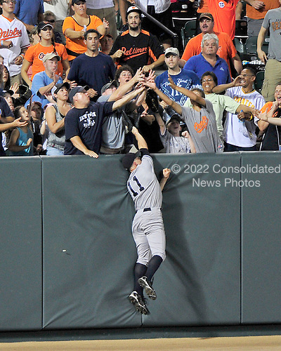 New York Yankees left fielder Brett Gardner (11) leaps but cannot catch Baltimore Orioles catcher Matt Wieters' sixth inning 3 run home run against the Baltimore Orioles at Oriole Park at Camden Yards in Baltimore, MD on Friday, August 26, 2011.  The Orioles won the game 12 - 5..Credit: Ron Sachs / CNP.(RESTRICTION: NO New York or New Jersey Newspapers or newspapers within a 75 mile radius of New York City)