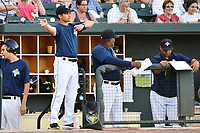 Manager Jose Leger (19) of the Columbia Fireflies, left, signals to fielders in a game against the West Virginia Power on Friday, May 19, 2017, at Spirit Communications Park in Columbia, South Carolina. On his left are pitching coach Jonathan Hurst and hitting coach Joel Fuentes. West Virginia won, 3-1. (Tom Priddy/Four Seam Images)