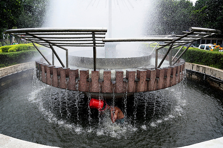 A Bangladeshi boy bathes at an artificial waterfall, which was made for beautification of Dhaka early morning in Dhaka, Bangladesh.