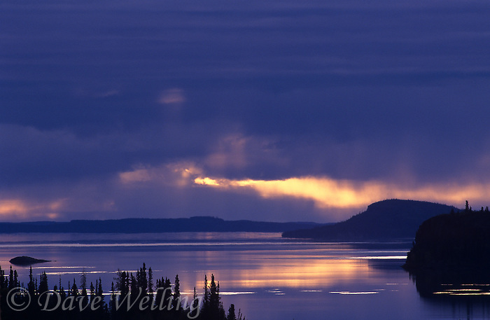 731000237 the setting sun shines through the thick cloud cover of a summer storm above great slave lake in the northwest territories in canada