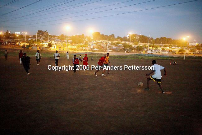SOWETO, SOUTH AFRICA OCTOBER 23: A soccer team practice in a field after dark on October 23, 2006 in Motswaledi section of Soweto, Johannesburg, South Africa. Soweto is South Africa?s largest township and it was founded about one hundred years to make housing available for black people south west of downtown Johannesburg. The estimated population is between 2-3 million. Many key events during the Apartheid struggle unfolded here, and the most known is the student uprisings in June 1976, where thousands of students took to the streets to protest after being forced to study the Afrikaans language at school. Soweto today is a mix of old housing and newly constructed townhouses. A new hungry black middle-class is growing steadily. Many residents work in Johannesburg, but the last years many shopping malls have been built, and people are starting to spend their money in Soweto.  .(Photo by Per-Anders Pettersson/Getty Images)..