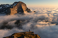 Hiker on summit of Helvetestind mountain peak takes in view over coastal fog, Moskenesøy, Lofoten Islands, Norway