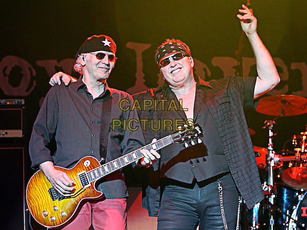 Paul Dean and Mike Reno.Legendary hit rockers Loverboy opened for Journey in Atlanta on their 2012 tour at Aaron's lakewood Amphitheater, Atlanta, GA., USA..October 6th, 2012 .on stage in concert live gig performance performing music half length black shirt sunglasses shades pink guitar arm in air.CAP/ADM/DH.©Dan Harr/AdMedia/Capital Pictures.