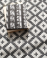 Esparto, a hand-cut tumbled mosiac, shown in Nero Marquina and Calacatta , is part of the Tissé™ collection for New Ravenna.