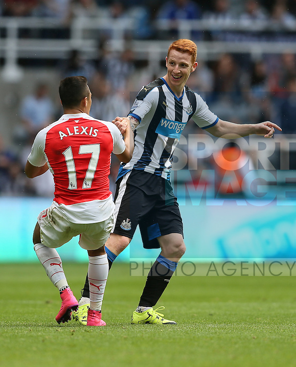 Jack Colback of Newcastle United laughs as he helps Alexis Sanchez of Arsenal to his feet - English Premier League - Newcastle Utd v Arsenal - St James' Park Stadium - Newcastle - England - 28th August 2015 - Picture Simon Bellis/Sportimage