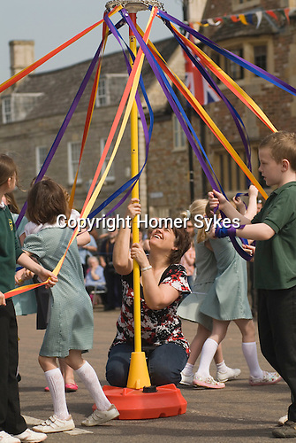 Stilton village May Fair. Primary village school teacher holding up childrens May Pole dancing. Cambridgeshire UK 2008.