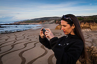 A young woman uses her phone to take a picture of a sandy beach transformed into a temporary work of art.  Pescadero State Beach on the California coast.