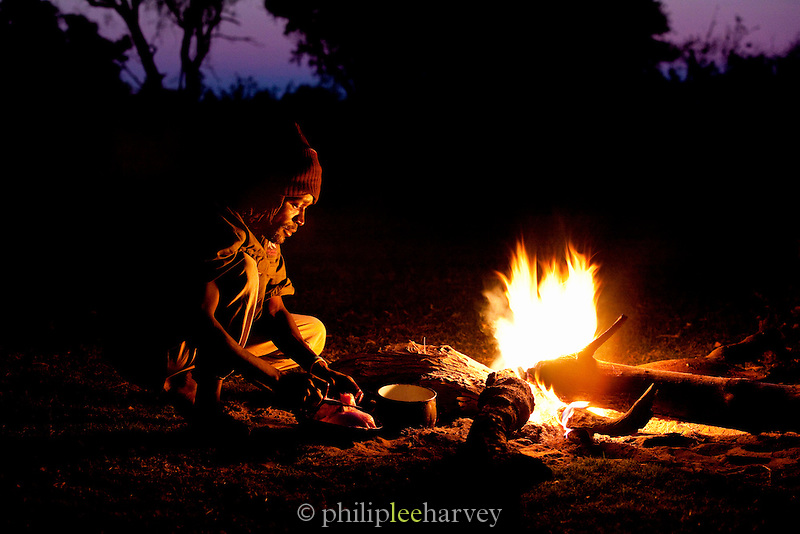 A local guide prepares food over an open camp fire in the Okavango Delta, Botswana