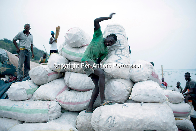 LISALA, DEMOCRATIC REPUBLIC OF CONGO APRIL 1: A dock worker carries a heavy bag of maize on a boat with destination Kinshasa on April 1, 2006 in Lisala, Congo, DRC. The boat was loaded with hundreds of maize bags, palm oil etc, The Congo River is a lifeline for millions of people, who depend on it for transport and trade. The journey from Kisangani to Kinshasa is about 1750 kilometers, and it takes from 3-7 weeks on the river, depending on the boat. Passengers usually sleep in the open, often on top of maize bags or other cargo. The boat carries many animals such as pigs, goats, crocodiles, monkeys, lizards, etc. During the Mobuto era, big boats run by the state company ONATRA dominated the traffic on the river. These boats had cabins and restaurants etc. All the boats are now private and are mainly barges that transport goods. The crews sell tickets to passengers who travel in very bad conditions, mixing passengers with animals, goods and only about two toilets for five hundred passengers. The conditions on the boats often resemble conditions in a refugee camp. Congo is planning to hold general elections by July 2006, the first democratic elections in forty years. (Photo by Per-Anders Pettersson)..