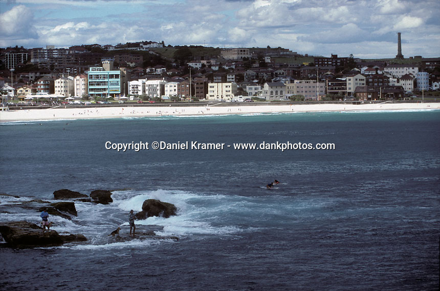 Two fishermen try their luck as two surfers paddle out at Bondi Beach in 1995.