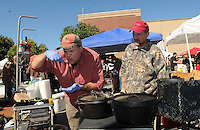 """NWA Democrat-Gazette/FLIP PUTTHOFF <br /> TREE CUISINE<br /> Jim Fishback of Bentonville (left) and Johnnie Green of Rogers check the taste of their Italian squirrel dish on Saturday Sept. 12 2015 during the third annual World Championship Squirrel Cookoff in downtown Bentonville. Teams of squirrel chefs prepared an array of dishes with squirrel meat, such as gumbo, meatballs and stuffed peppers. The team """"Bud and Bones"""" comprised of Jeff Terry of Pea Ridge, Dan Judd of Rogers and Tim Owens of Bella Vista won the cookoff with their dish, empanadas with spanish cream rice. Money raised at the event benefited Sheep Dog Impact Assistance, which aids military and law enforcement personnel, said Joe Wilson, cookoff chief."""